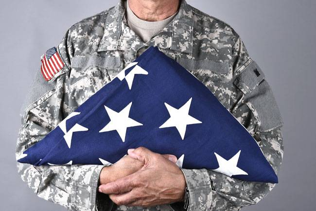 A solider holding a folded flag